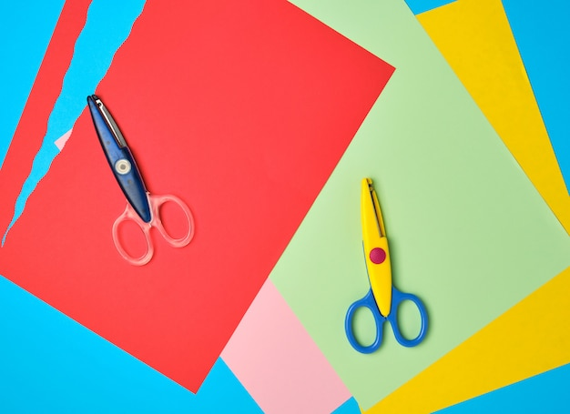 Plastikschere und farbiges papier zum schneiden von figuren