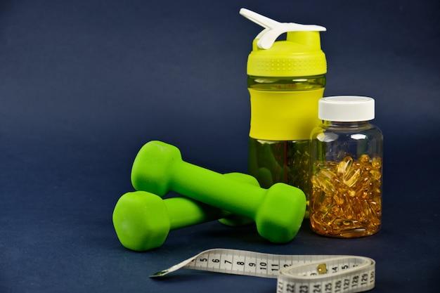 Plastikshaker, grüne hanteln und eine dose omega 3