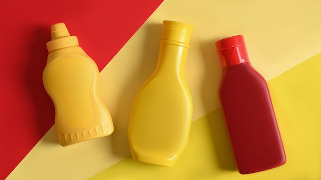 Plastiksoßenflaschen auf gelbem und gelesenem hintergrund.