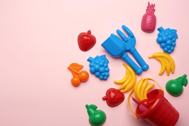 Plastikspielzeug für kinder in form von früchten und einem eimer auf einem rosa hintergrund