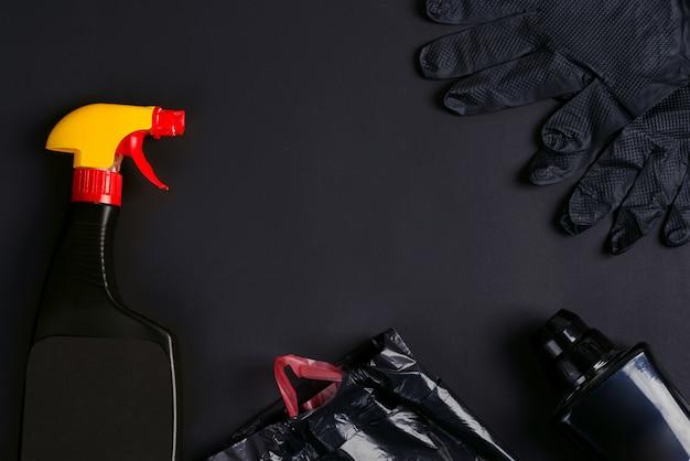 Plastiksprühflaschen, müllsäcke und gummihandschuhe auf einem schwarzen hintergrund.