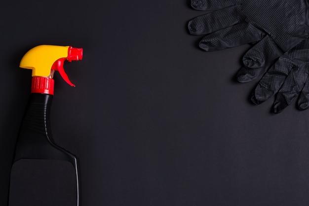Plastiksprühflaschen und gummihandschuhe auf einem schwarzen hintergrund. reinigungskonzept