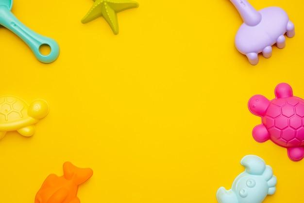 Plastikstrandspielzeugpastellfarbe auf gelbem hintergrund. die entwicklung des feinmotorkonzepts. kreativitätsspiel und sommerkonzept draufsicht