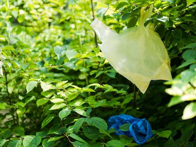 Plastiktasche, die am baumast am garten hängt