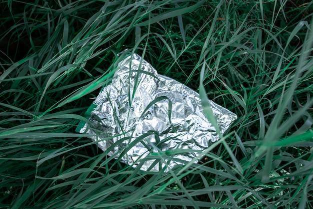 Plastiktasche im grünen gras, naturverschmutzungskonzept. stück plastikabfall (leeres lebensmittelpaket) weggeworfen auf einen rasen, großaufnahme