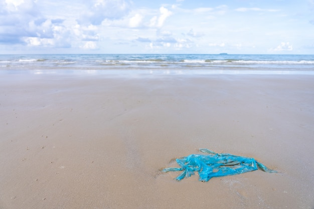 Plastiktüte auf dem sandstrand, küstenstrand säubernd.