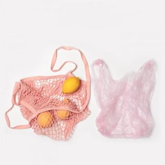 Plastiktüte aus kunststoff und rosa baumwolltasche umweltfreundlich. das konzept des vergleichs. ohne kunststoff kein abfall. hellgrauer hintergrund mit kopierraum. früchte, zitronen. niemand