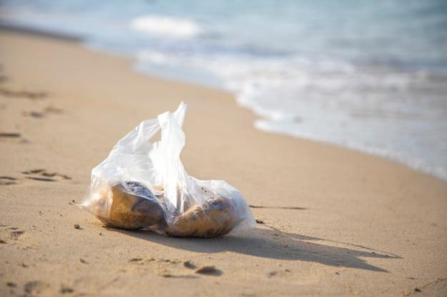 Plastiktüte, die an einem tropischen sandstrand liegt. umweltverschmutzung. müll im meer