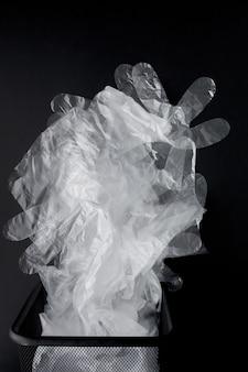 Plastiktüte mit griffen, handschuhe im behälter auf schwarzem hintergrund. gebrauchte plastiktüte zum recycling. konzept - ökologie, planetenverschmutzung mit kunststoff-zellophan-polyethylen