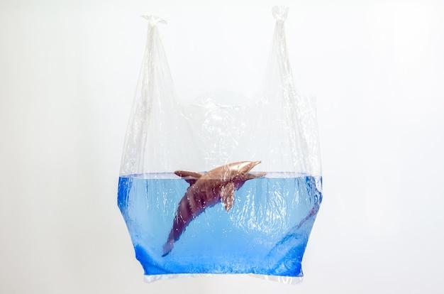 Plastiktüte mit verschwommenem delphin-spielzeugmodell in der wasseroberfläche auf weißem hintergrund