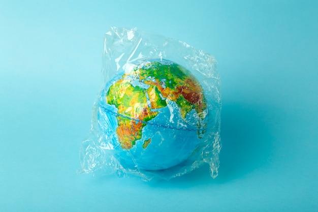 Plastiktüte verschmutzungskonzept. erdkugel in einer plastiktüte auf einem farbigen hintergrund. plastik- und abfallverschmutzungsmeere, natur