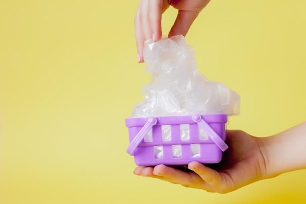 Plastiktüten in der hand im einkaufskorb auf gelb