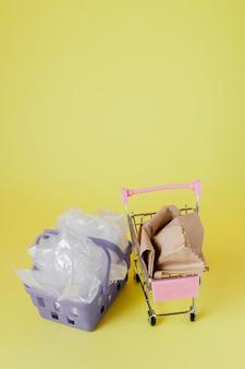 Plastiktüten und papiertüten in einem einkaufskorb auf gelb