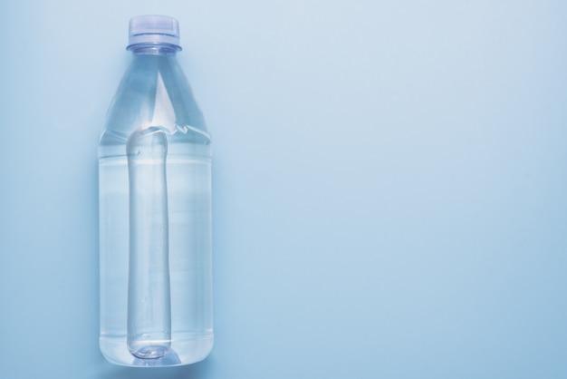 Plastikwasserflasche auf blauem oberflächenhintergrund