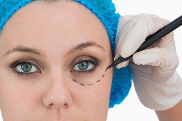 Plastischer chirurg, der auf das gesicht der ernsten frau schreibt