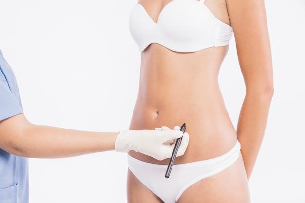 Plastischer chirurg, der bleistift nahe frauenkörper hält