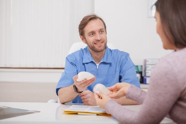 Plastischer chirurg, der einem patienten brustimplantate zeigt