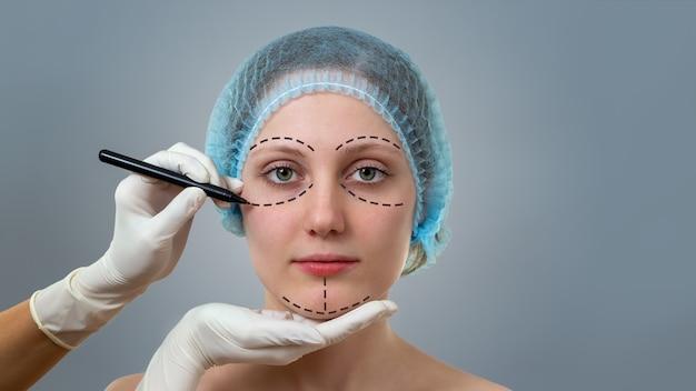 Plastischer chirurg, der linien auf einem gesicht der jungen frau vor der schönheitsoperation zeichnet