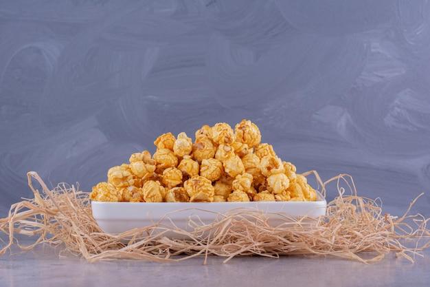 Platte auf einem haufen stroh gefüllt mit einem haufen popcorn-süßigkeiten auf marmorhintergrund. foto in hoher qualität