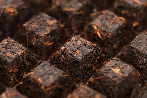 Platte aus schwarzem tee nahaufnahme. chinesische puer. foto in hoher qualität