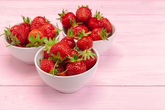 Platte der erdbeere auf rosa hölzernem hintergrund