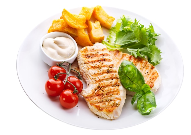 Platte der gegrillten hühnerbrust mit gemüse lokalisiert auf weiß