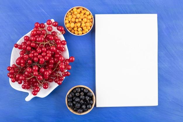Platte der roten johannisbeere und schalen der acai-beere und des sanddorns neben weißer tafel auf blauem hintergrund. hochwertiges foto