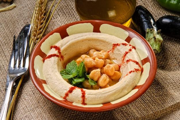 Platte des arabischen traditionellen hummus mit erbsenkörnern.