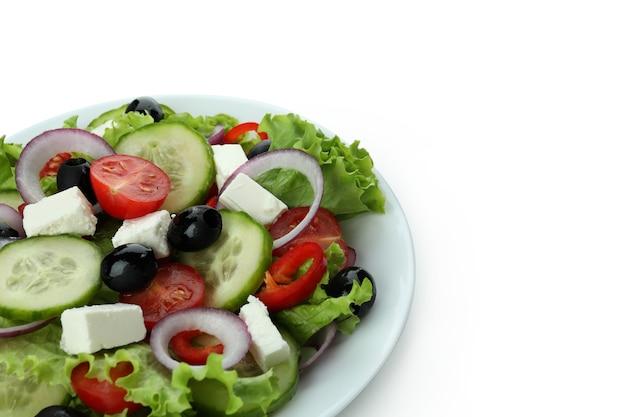 Platte des griechischen salats lokalisiert auf weißer oberfläche