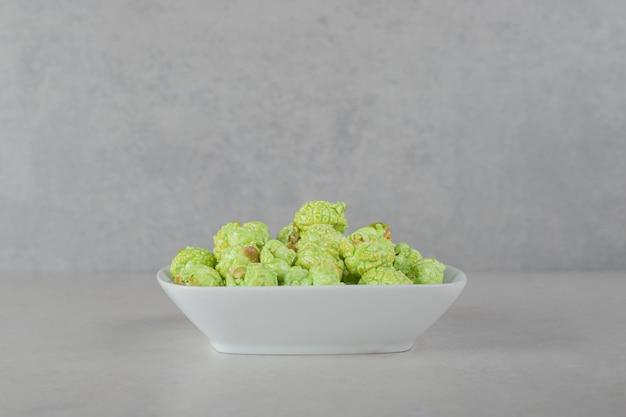 Platte des grünen kandierten popcorns auf marmorhintergrund.