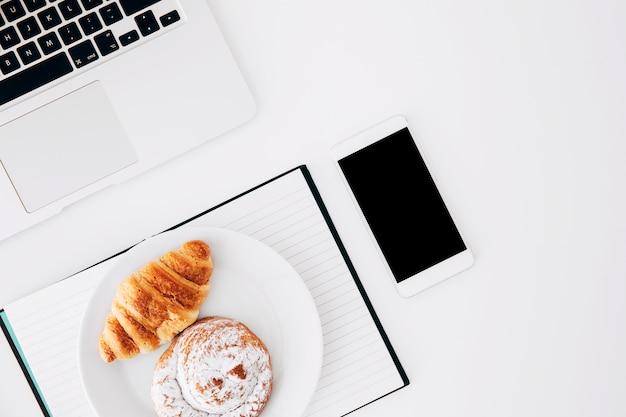 Platte des hörnchens und der brötchen auf tagebuch mit smartphone und laptop auf weißem hintergrund