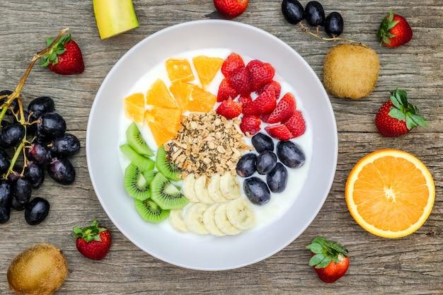 Platte des natürlichen weißen joghurts mit müsli, orange, banane, kiwi, erdbeeren und trauben trägt früchte. joghurt und obst als zutaten rund um den teller. ansicht von oben. gesundes konzept.