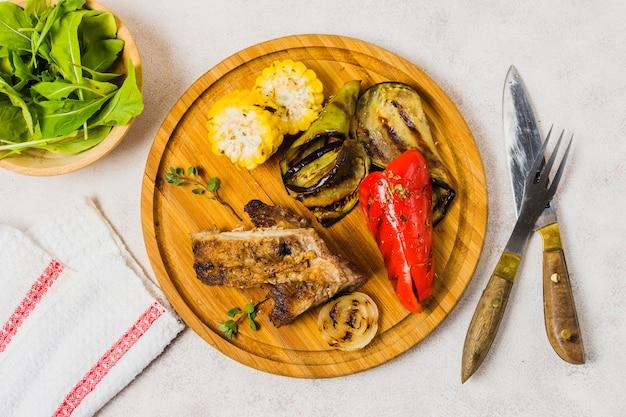 Platte diente mit gebratenem gemüse und fleisch auf tabelle