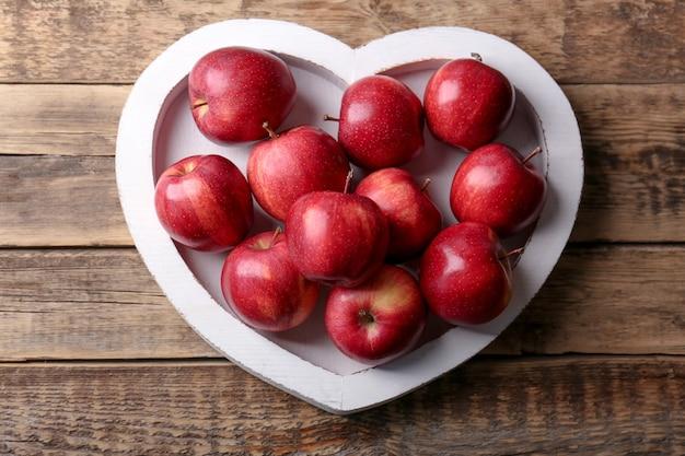 Platte in form des herzens mit frischen roten äpfeln auf holztisch