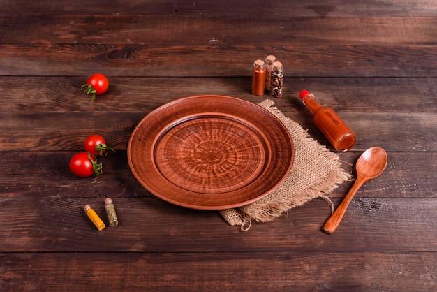 Platte, löffel, gewürze und anderes küchenzubehör auf einem dunklen hölzernen hintergrund