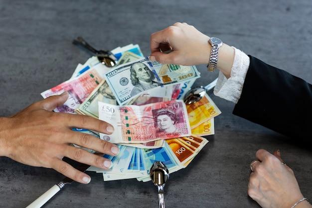Platte mit amerikanischen und israelischen rechnungen. hand des mannes und bündel bargeld auf weißem teller auf dem tisch. konzept, das geldgier zeigt. geschäftsleute, die geld nis greifen. hände, die versuchen, geld zu ergattern