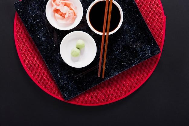 Platte mit asiatischen gewürzen und essstäbchen