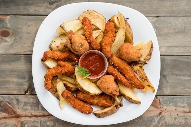 Platte mit brathähnchen und kartoffeln