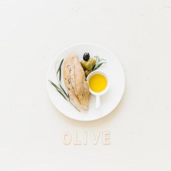 Platte mit brotoliven und -öl mit olivgrünem wort