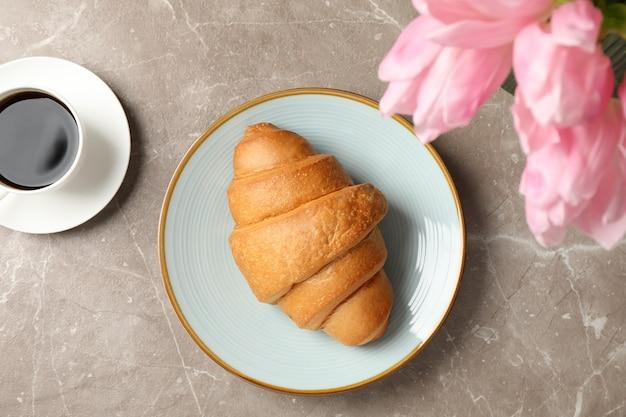 Platte mit croissant auf grauem hintergrund mit tulpen und tasse kaffee, draufsicht