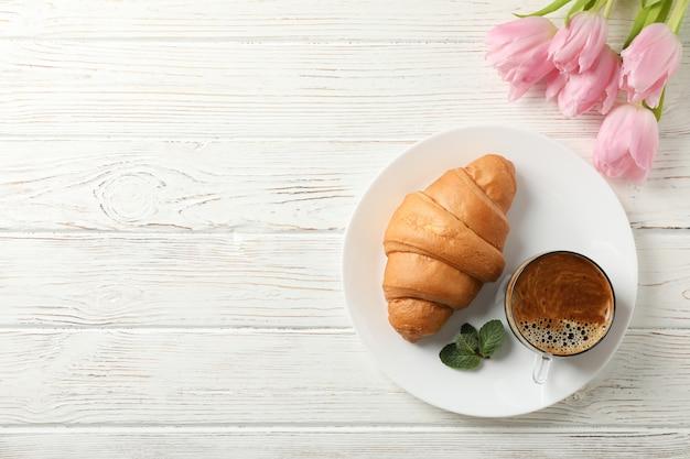 Platte mit croissant auf hölzernem hintergrund mit tulpen, draufsicht