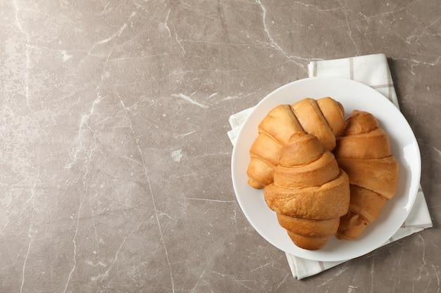 Platte mit croissants auf grauem hintergrund, draufsicht