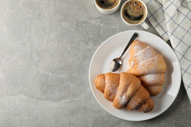 Platte mit croissants, tassen kaffee und handtuch auf grauem hintergrund, draufsicht