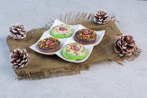 Platte mit donuts inmitten von tannenzapfen auf einem stück stoff auf einem marmortisch.