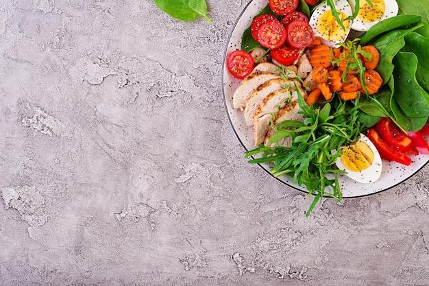 Platte mit einem ketodiätfutter. kirschtomaten, hühnerbrust, eier, karotten, salat mit rucola und spinat. keto-mittagessen. draufsicht