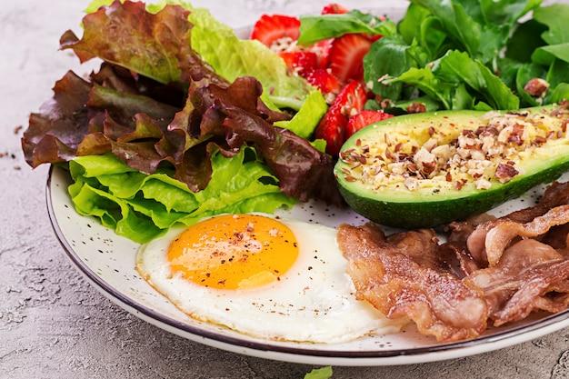 Platte mit einem ketodiätfutter. spiegelei, speck, avocado, rucola und erdbeeren. keto frühstück.