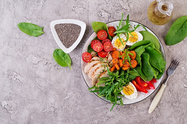 Platte mit einem ketodiätlebensmittel. kirschtomaten, hähnchenbrust, eier, karotten, salat mit rucola und spinat. keto-mittagessen. ansicht von oben