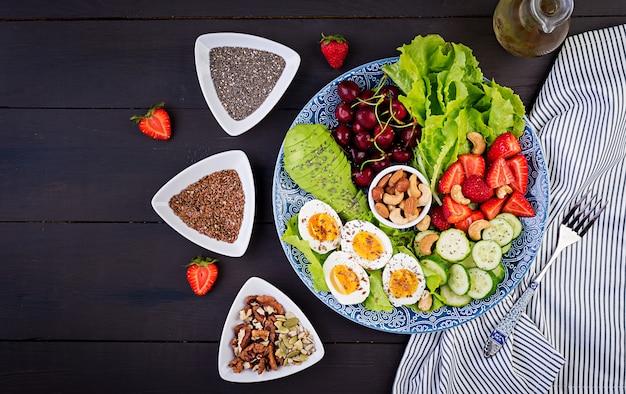 Platte mit einem paläo-diätfutter. gekochte eier, avocado, gurke, nüsse, kirsche und erdbeeren. paleo frühstück. draufsicht
