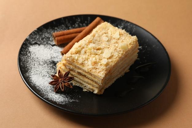 Platte mit einem stück napoleon-kuchen mit zimt auf der basteloberfläche
