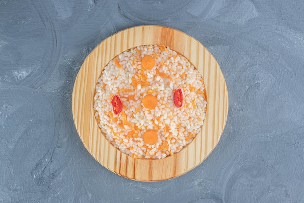 Platte mit einer erfüllenden portion gekochtem reis auf marmortisch.
